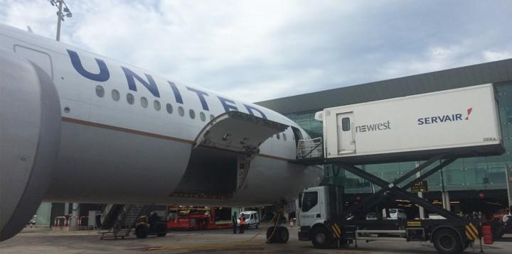 Avion de la compagnie United Airlines au sol, avec un camion de Newrest Servair